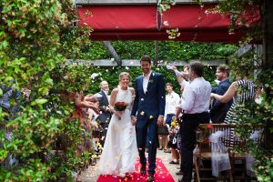 Just married! Nik and Brianne enjoying the rose petals in their recessional